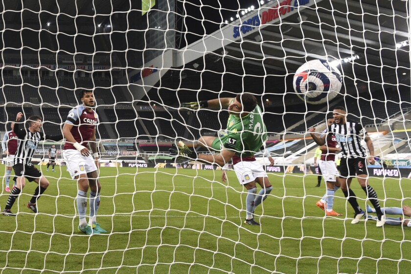 Aston Villa's goalkeeper Emiliano Martinez fails to save the goal from Newcastle's Jamaal Lascelles, right, during the English Premier League soccer match between Newcastle United and Aston Villa at the St James' Park stadium in Newcastle, England, Friday, March 12, 2021. (Stu Forster/Pool via AP)