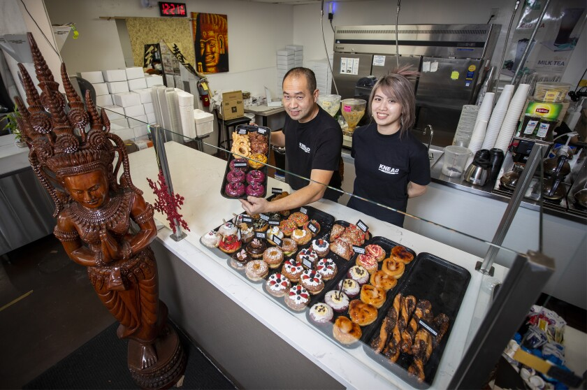 Two donut shop proprietors pose with their wares
