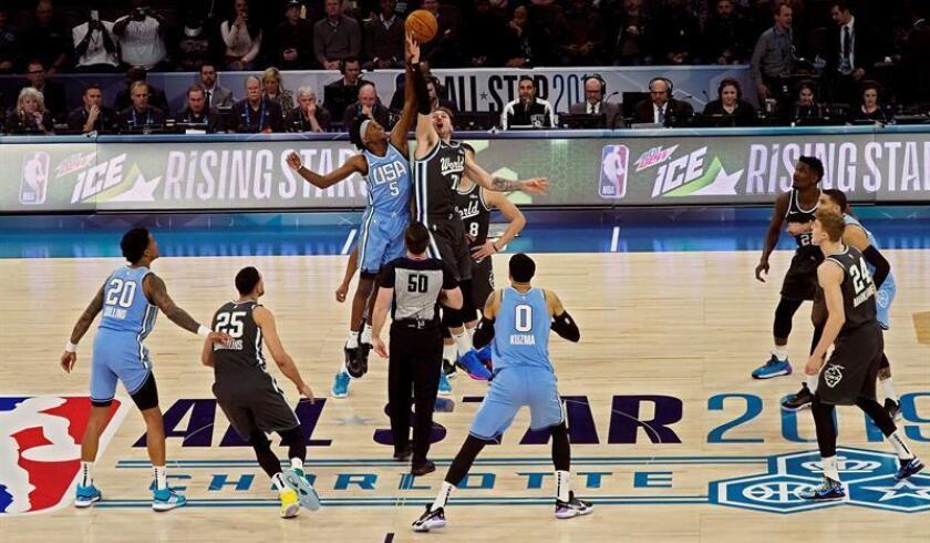 El jugador del Equipo del Mundo Luka Doncic, de Eslovenia (c-d), intenta atrapar el balón ante De'Aaron Fox (c-i), del Equipo de Estados Unidos, ante la mirada de Kyle Kuzma (c), durante el Partido de las Futuras Estrellas de la NBA, este viernes en el Spectrum Center de Charlotte (EE.UU.). EFE