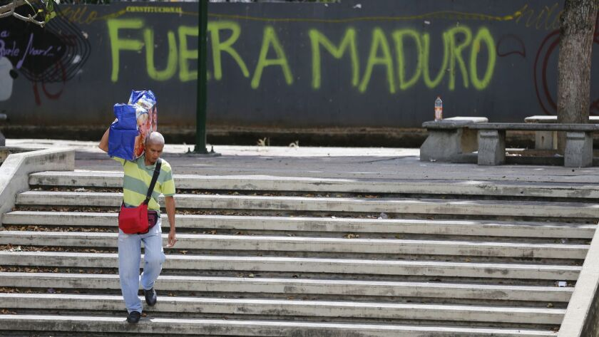"""A man walks past graffiti on the wall of a vacant lot that reads in Spanish: """"Get out Maduro,"""" refer"""