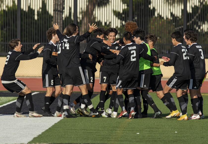Huntington Beach's Carson Dykes, center, is mobbed by his team after scoring a goal against Estancia.