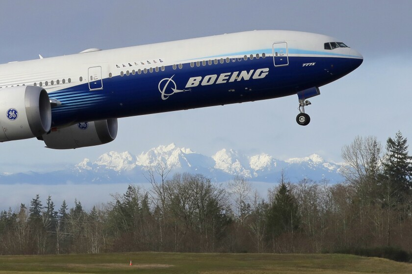 A Boeing 777 flies over fields with the Olympic Mountains in the background at Paine Field in Everett, Wash.