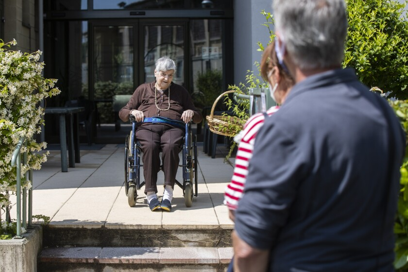 Carmela Bergamelli, 87, sits in a wheelchair at a safe distance as she talks to her family at the Martino Zanchi Foundation nursing home in Alzano Lombardo, Italy, Friday, May 29, 2020. (AP Photo/Luca Bruno)