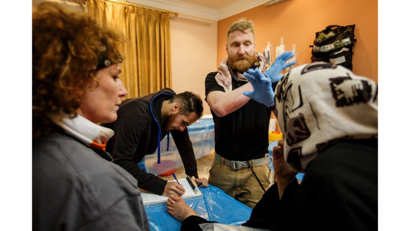 """Dr. Cornelius """"Woody"""" Peeples, tries to speak his concerns in Arabic to a woman showing symptoms of diabetes at a field clinic operated by medics from the Iraqi Emergency Response Division and New York City Medics near the front lines in Mosul."""