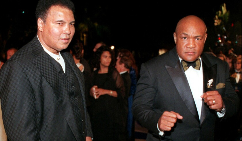 Muhammad Ali, left, and George Foreman arrive at a Vanity Fair Oscar party.