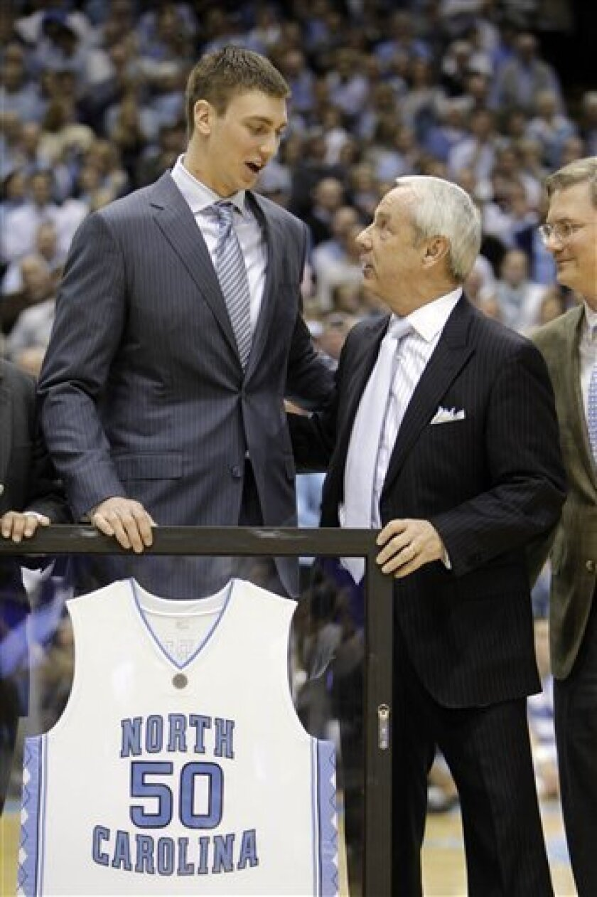 Former North Carolina player Tyler Hansbrough, left, talks with coach Roy Williams during a ceremony retiring Hansbrough's number at halftime of an NCAA college basketball game against Duke in Chapel Hill, N.C., Wednesday, Feb. 10, 2010. (AP Photo/Chuck Burton)