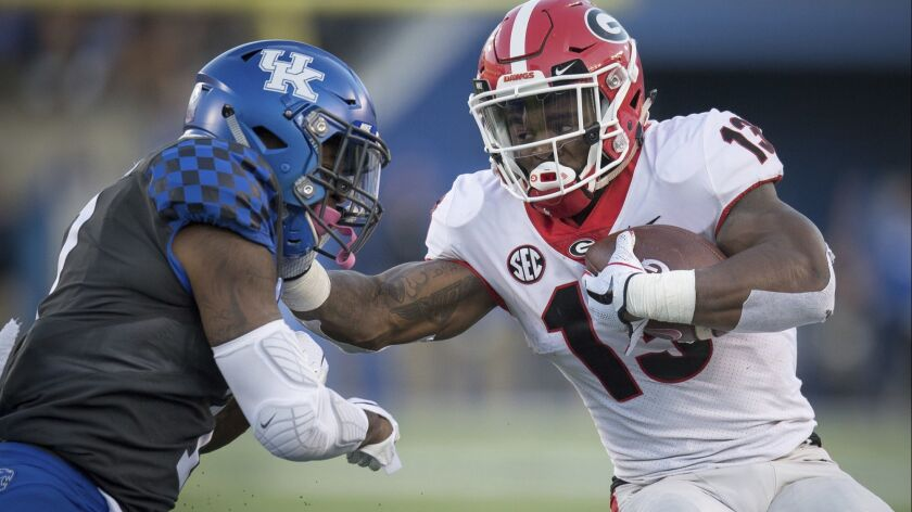 Georgia running back Elijah Holyfield (13) stiff arms Kentucky safety Mike Edwards (7) during the second half on Saturday.