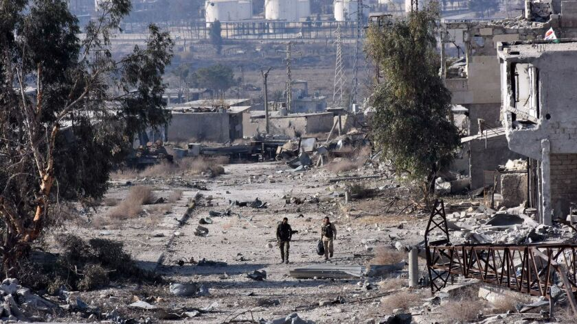 Syrian pro-government forces patrol Aleppo's Sheikh Saeed district Monday after troops retook the area from rebel fighters.