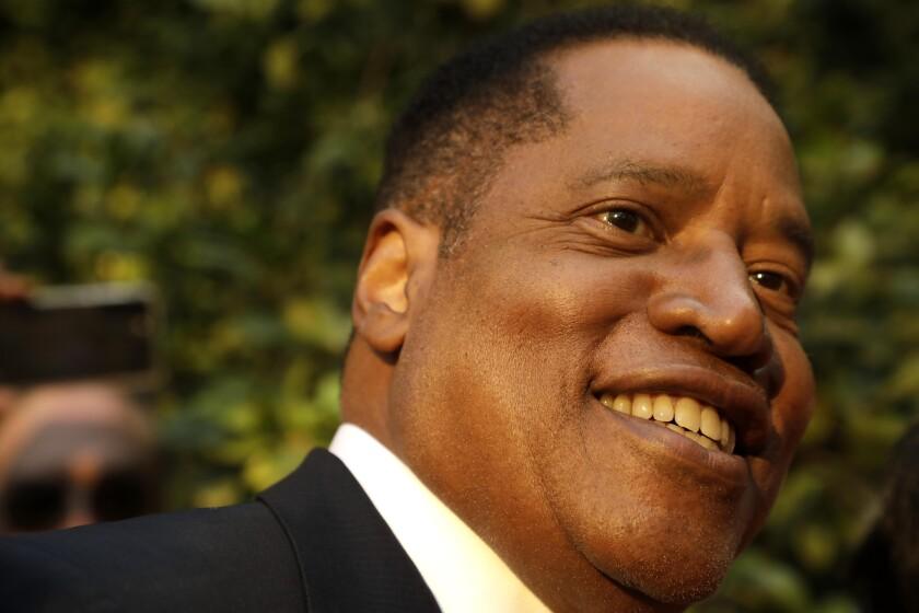 A closeup of Larry Elder, smiling.