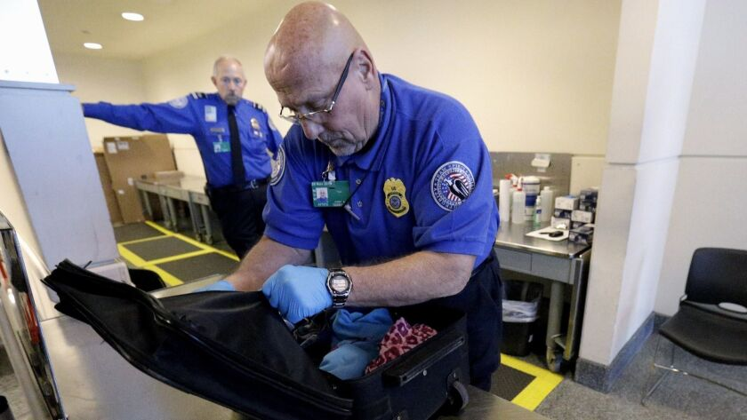 In this Nov. 21, 2014 photo, a Transportation Security Administration agent checks a bag at a security checkpoint area at Midway International Airport in Chicago. To reduce turnover, the TSA has proposed a new training program, but the union for screeners is not impressed.