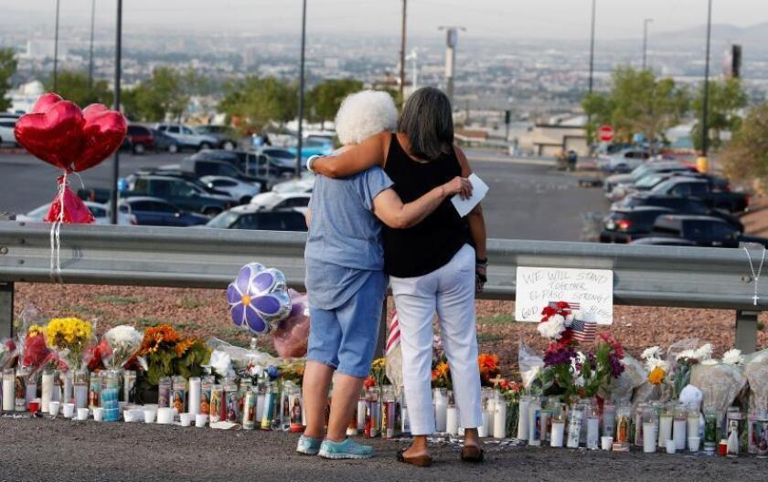 Emma Del Valle (i) abraza a Brenda Castañeda (R) en el memorial dedicado a las víctimas del tiroteo masivo que ocurrió en un Walmart en El Paso, Texas.