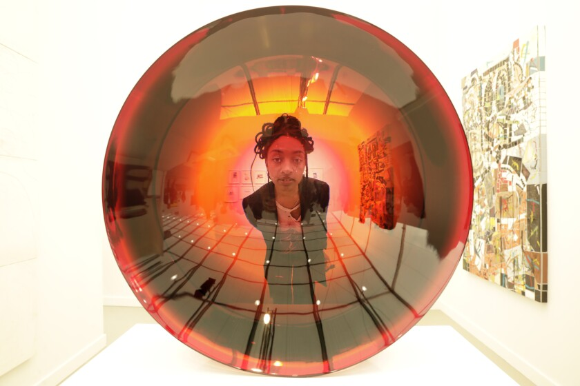 """Artist Aria Dean looks through """"Untitled (parabolic lens)"""" by Fred Eversley at the David Kordansky Gallery booth at Frieze Los Angeles during the Thursday preview of the show."""