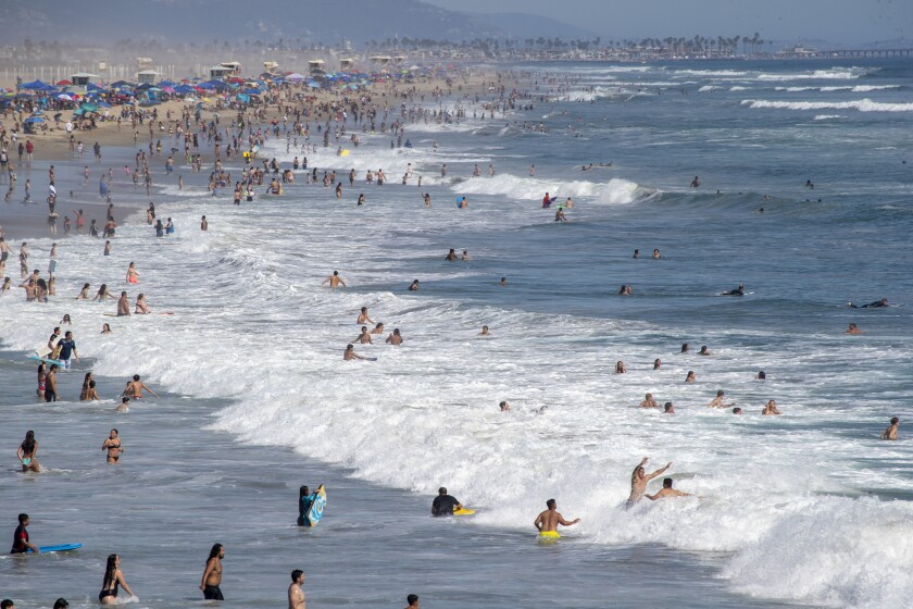 Beach goers take to the water to cool off amid high temperatures in Huntington Beach.