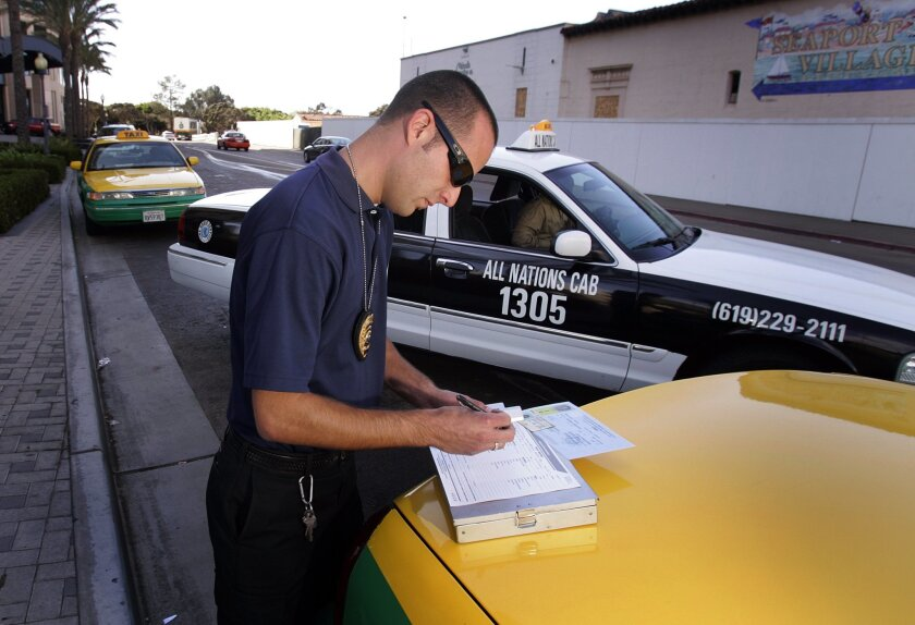 MTS field inspector Kris Harrington wrote a citation during a taxi inspection yesterday near Seaport Village. MTS stepped up its inspections last year.