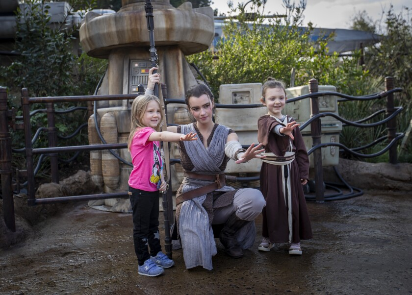 A cast member dressed as Rey poses for a photo with Penny, left, and Adelaide Remaklus of Ferndale, Wash., at Disneyland.
