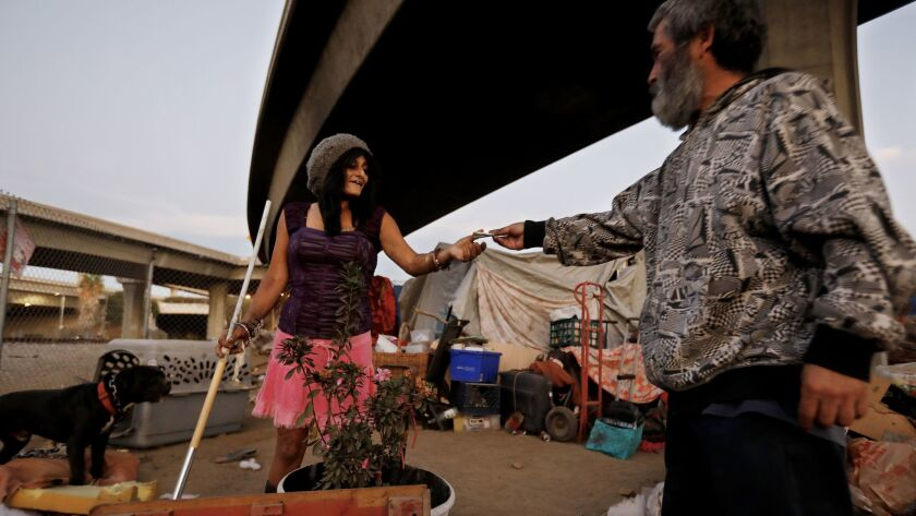 Samantha Sandoval, 40, left, is given a dollar by Margarito Alvarez, 56, her neighbor, at her tent where she has lived for a year at a homeless camp along West 117th Street and South Broadway in Los Angeles.