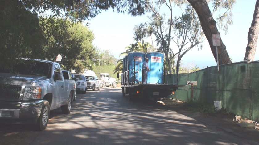 Trucks park against hedges, and on the opposite, 'No Parking' side, a truck delivers portable toilet