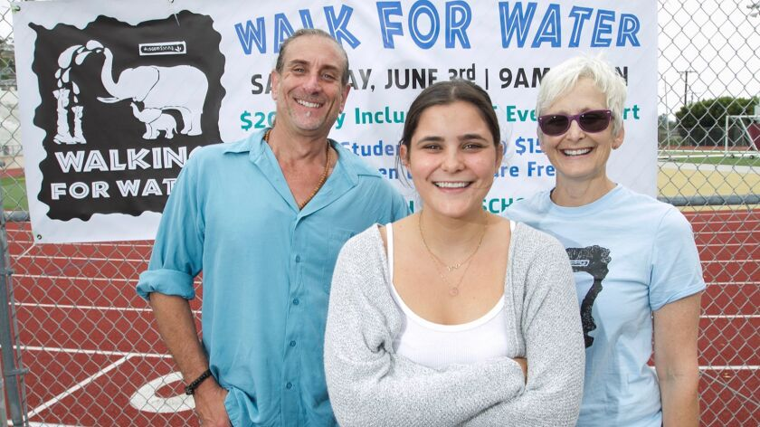 Charlotte Watkins, president of the student Walking for Water Club, center, stands with Greg Friedma