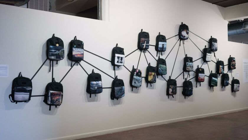 An installation of backpacks printed with photographs taken by BorderClick participants.