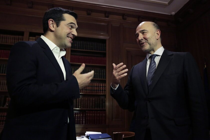 Greek Prime Minister Alexis Tsipras, left, meets with European Commissioner for Economic and Financial Affairs Pierre Moscovici in Athens, on Tuesday, Nov. 3, 2015. Moscovici's talks with officials in Greece's leftwing government will focus on  the progress of reforms demanded by the country's Euro