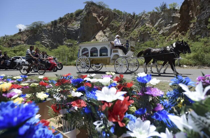 En esta imagen, una carroza tirada por caballos traslada los restos de Ángel Candelario Padro, un enfermero y miembro de la Guardia Nacional de 28 años, al cementerio municipal de Guanica, en Puerto Rico. Candelario Padro fue una de las 49 víctimas mortales de una balacera en un club nocturno gay de Orlando, Florida. (AP Foto/Carlos Giusti)
