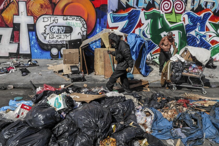 Piles of trash remain at the corner of East 10th Street and Naomi Avenue in downtown Los Angeles.