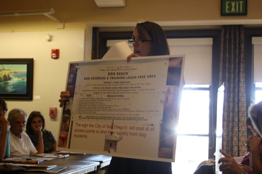 Barber Tract resident Cynthia Chasan shows a sign of what might be required if the off-leash area is approved.