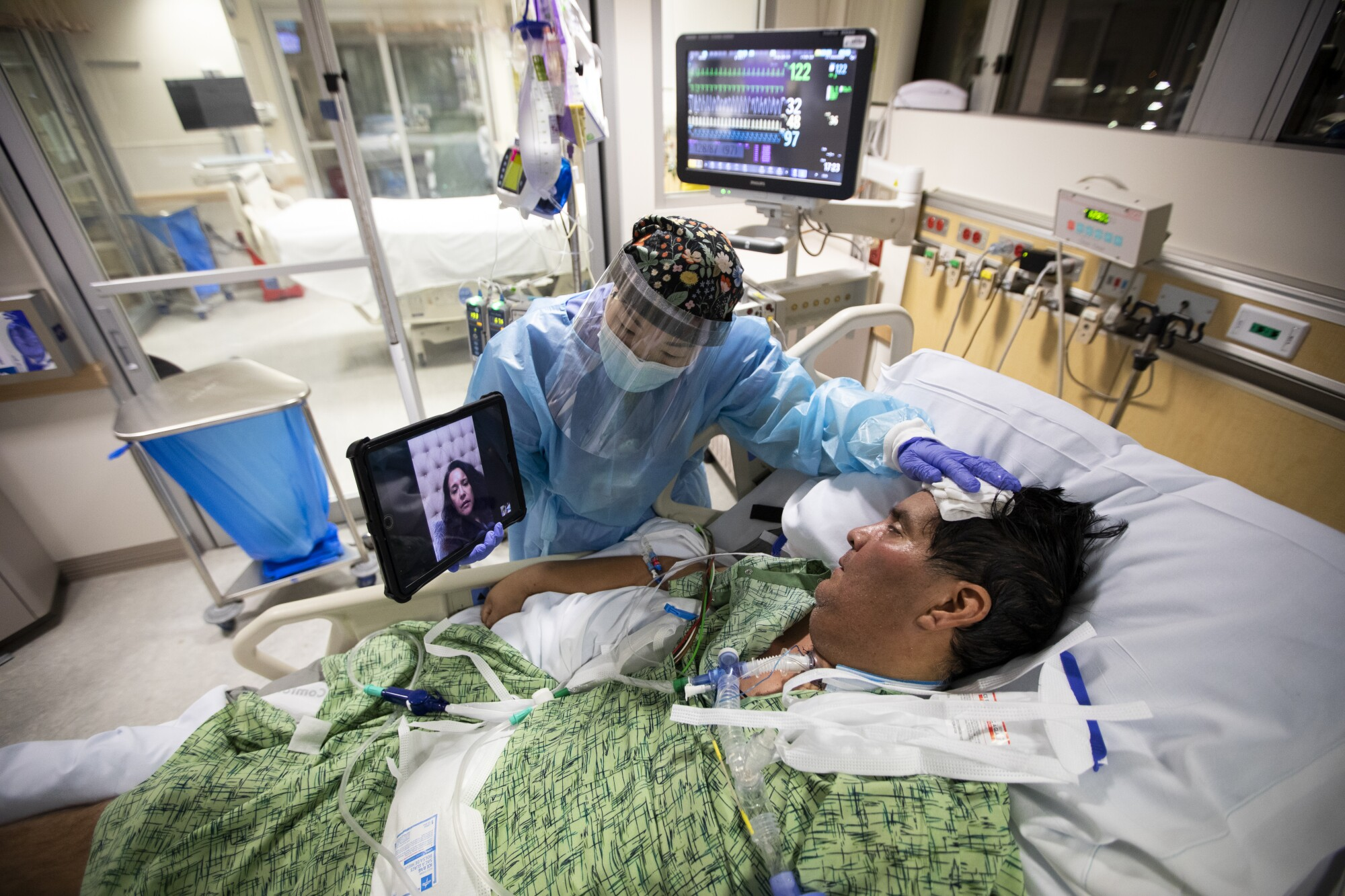 Kat Yi holds an iPad up to Eduardo Rojas, 50, so that his wife can see him inside the ICU