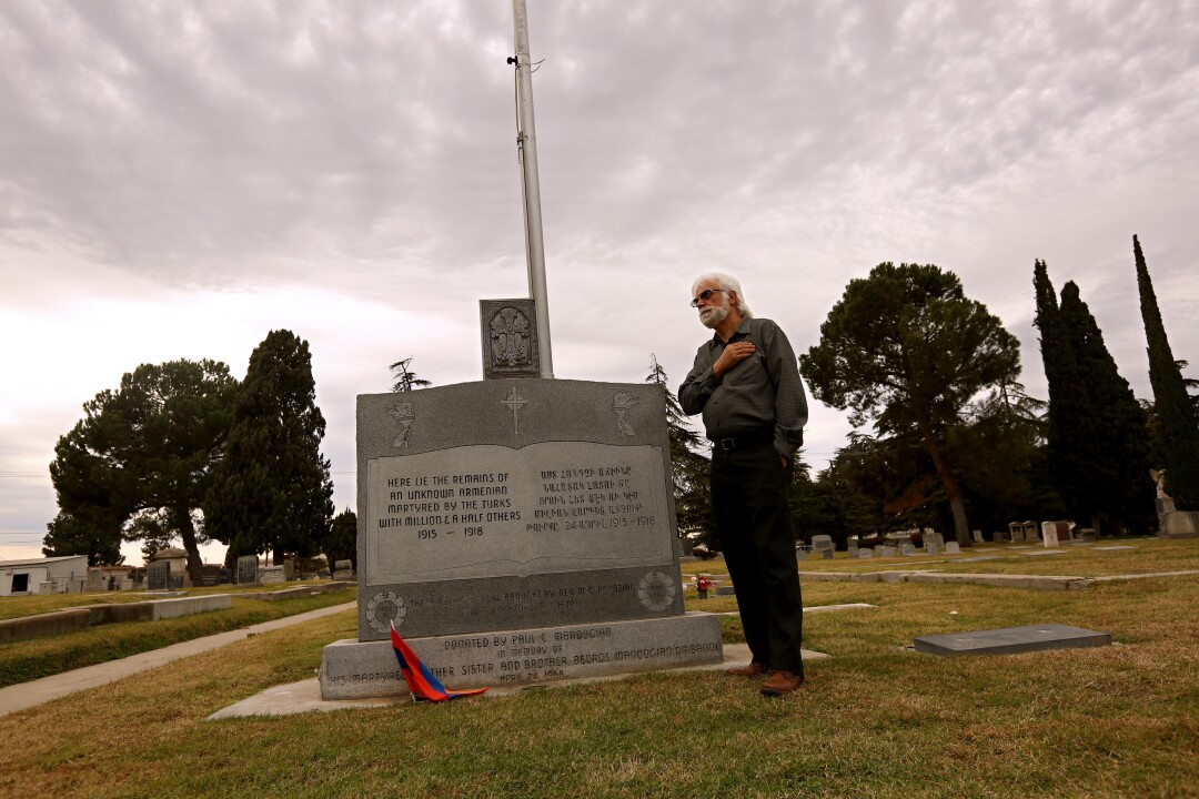 A man places his hand over his heart in front of a large gravestone in a cemetery