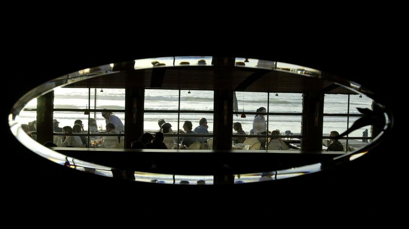 Guests and their servers, along with a great view of the ocean, is reflected in one of the mirrors i