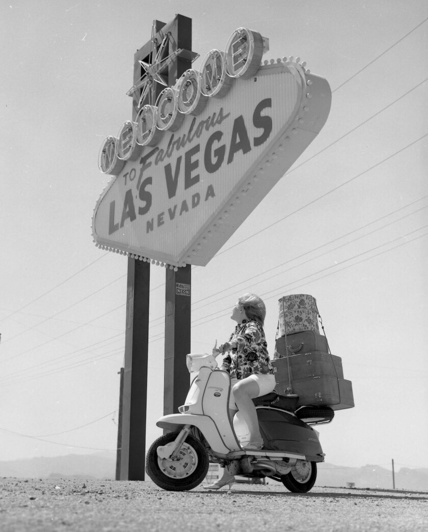 7/11/63 Welcome to Las Vegas sign with Diane Hertz on motor scooter. (Las Vegas News Bureau) 10467-