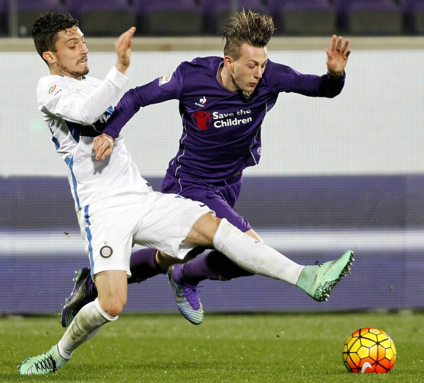 Fiorentina's Federico Bernardeschi, right, vies for the ball with Inter's Alex Telles during a Serie A soccer match between Fiorentina and Inter Milan at the Artemio Franchi stadium in Florence, Italy, Sunday, Feb. 14, 2016. (AP Photo/Fabrizio Giovannozzi)