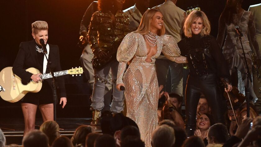 Beyoncé performs onstage with Martie Maguire of the Dixie Chicks at the 50th annual CMA Awards.
