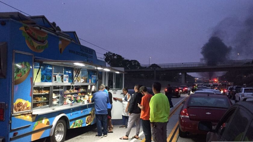 Commuters stuck on the westbound 105 Freeway form a line to buy snacks from a food truck that was among the vehicles caught in the traffic jam.