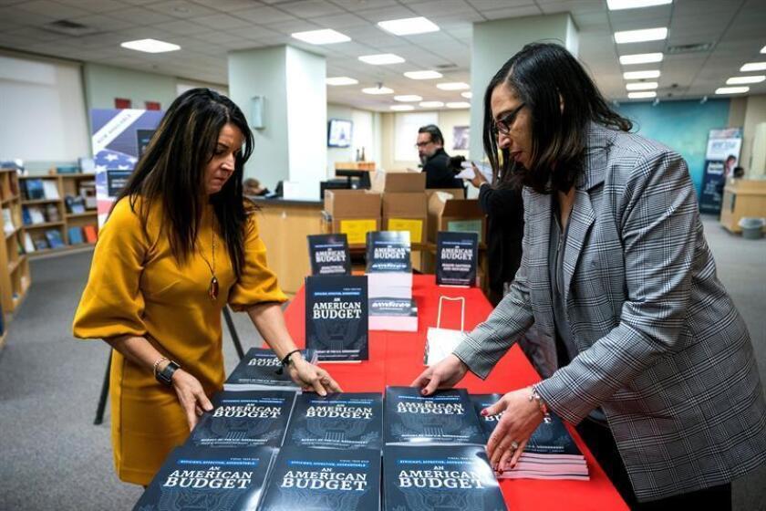 Las trabajadoras BethAnn Telford (i) y Berine Morrison (d) colocan ejemplares del Presupuesto fiscal para el año 2019, en una librería en Washington DC (Estados Unidos) hoy, 12 de febrero de 2018. EFE