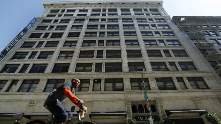 A bicyclist pedals along 6th Street in downtown Los Angeles, past the Santa Fe Lofts building. Completed in 1908 as offices, it had been converted to apartments and was just sold for nearly $70 million to a Sherman Oaks firm.