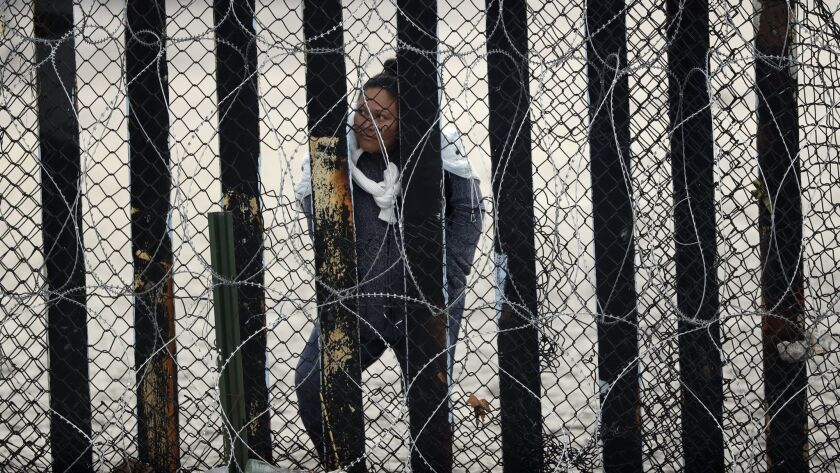 A woman in Tijuana, Mexico, looks through a section of the border wall lined with concertina wire Mo
