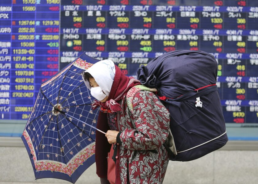 Elderly woman walks by an electronic stock board of a securities firm in Tokyo, Monday, Feb. 15, 2016. Tokyo's main share index, the Nikkei 225, jumped 4.4 percent to 15,615.84 in early trading Monday, helped by a weakening in the Japanese yen. (AP Photo/Koji Sasahara)