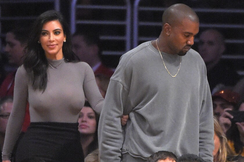 Kim Kardashian, left, and her husband, recording artist Kanye West, watch the Lakers play the Houston Rockets at Staples Center on Oct. 28, 2014.