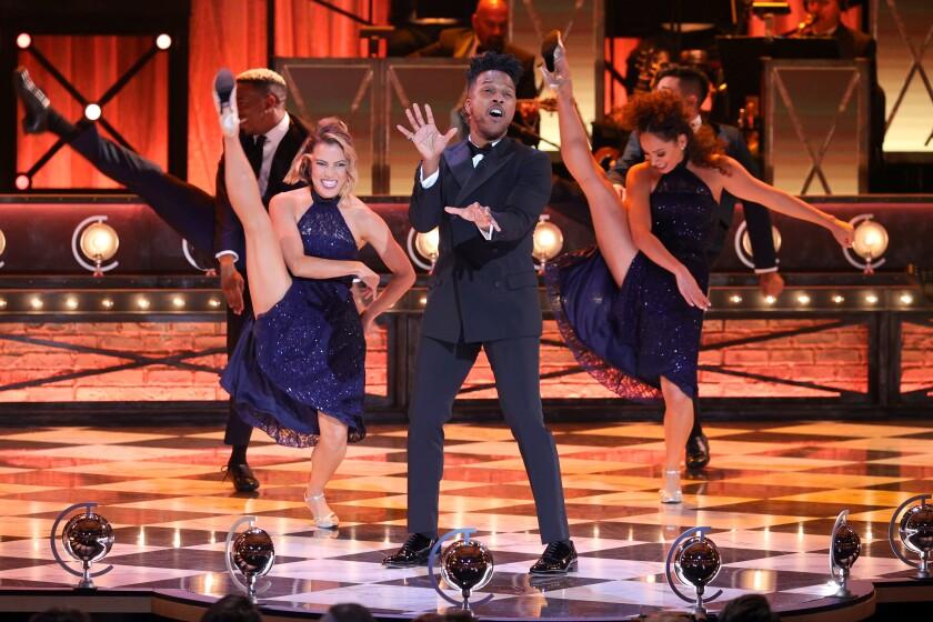 Leslie Odom Jr. sings with high-kicking dancers behind him.