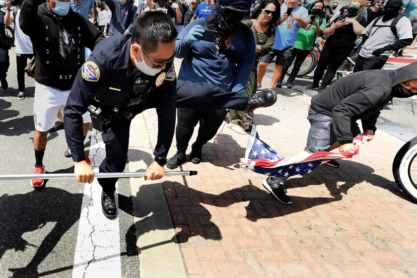 HUNTINGTON BEACH, CALIFORNIA APRIL 11, 2021-A young man steals an American flag from a White Lives Matter supporter as a Huntongton Beach police officer tries to stop it during a Black Lives Matter and White Lives Matter rally in Huntington Beach Sunday.(Wally Skalij/Los Angeles Times)