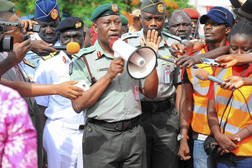 A Nigerian security officer speaks to protesters in Abuja. Demonstrators have been pressing the government to do more to find the 270 schoolgirls abducted in April by Islamist militants.