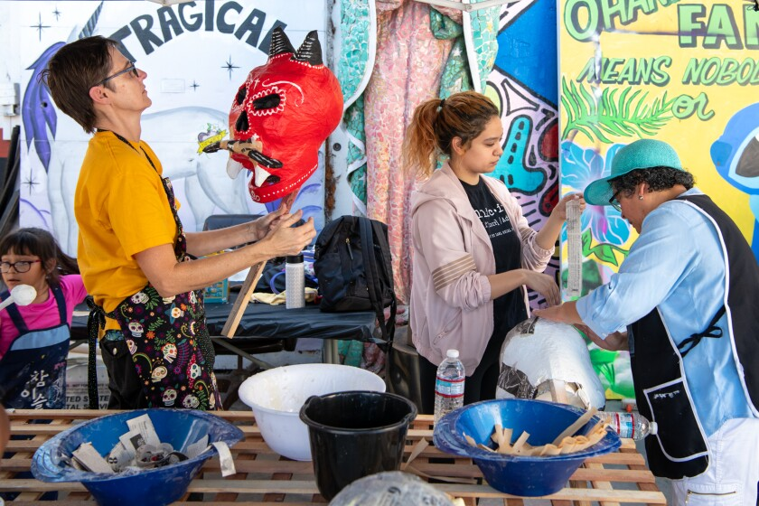 Kristen Johannesen, left, Olivia Ramos and her mother, Dora Magaña, work on papier-mache paper mache skulls for Day of the Dead at Self Help Graphics & Art.