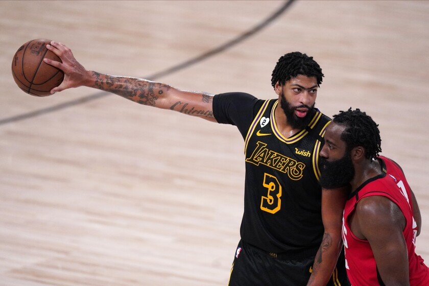 Lakers forward Anthony Davis extends his arm to protect the ball from Rockets guard James Harden during Game 2 on Sunday.