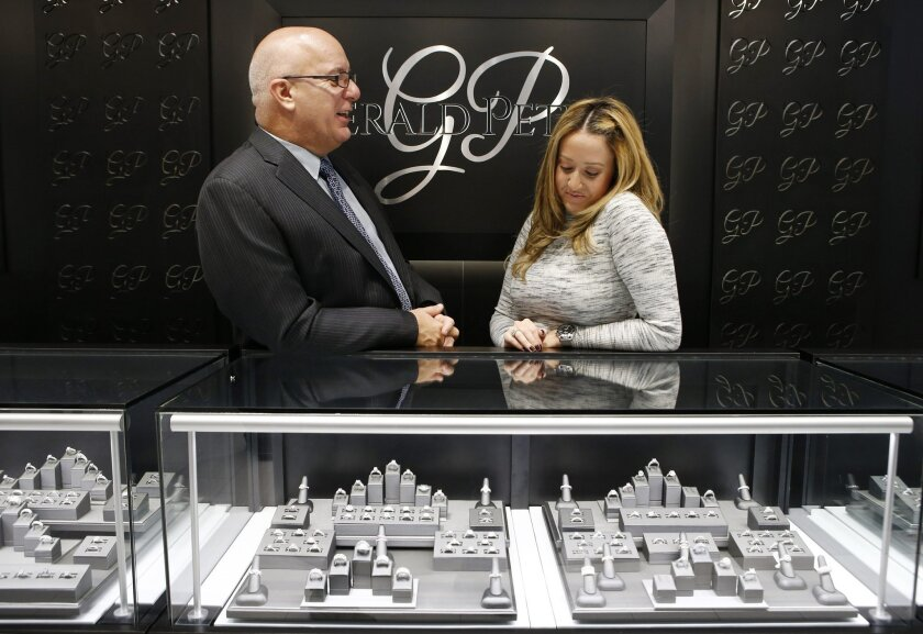 """In this Wednesday, Nov. 18, 2015, photo, business owner Jerry Amerosi, left, chats with employee Alana Fusco behind the counter at Gerald Peters, one of three stores he owns in the Staten Island Mall, in the Staten Island borough of New York. Amerosi's three stores in the mall will open at 6 p.m., on Thanksgiving and stay open until midnight. He'll have eight employees working, and if this Thanksgiving is anything like last year's, they'll have their hands full. """"It was crazy busy,"""" he said. (AP Photo/Kathy Willens)"""