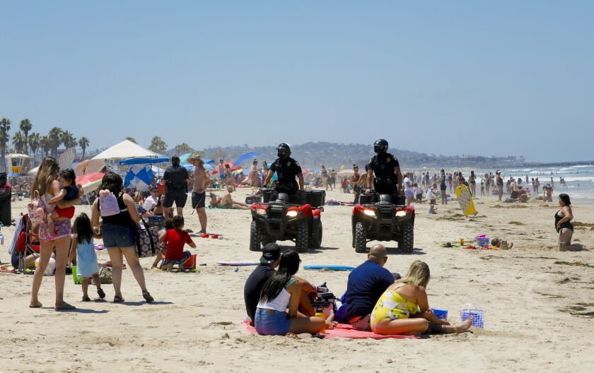 San Diego police officers patrol the beach in Mission Beach during the Fourth of July holiday.