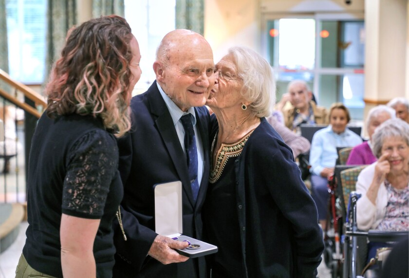 George Coburn, a 99-year-old World War II veteran, gets a kiss from his girlfriend Nancy Belknap as he holds his Purple Heart Medal, one of 11 long-overdue war honors he received Tuesday from U.S. Rep Mike Levin at a ceremony at Fairwinds Ivey Ranch retirement community in Oceanside. At left is George's granddaughter, Laura Coburn, of San Diego.