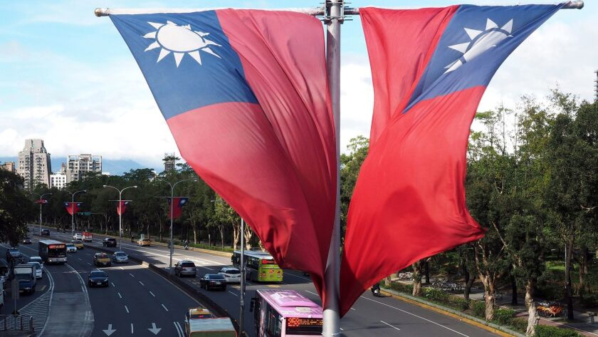 Traffic passes beneath Taiwan's national flags on a road in Taipei, Taiwan on Oct. 17, 2016.