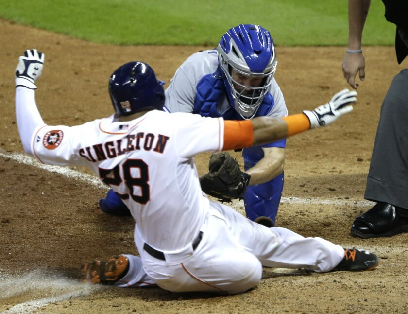 Houston Astros' Jon Singleton (28) avoids the tag from Toronto Blue Jays catcher Josh Thole at home plate in the eighth inning of a baseball game Saturday, Aug. 2, 2014, in Houston. Originally called out, the call was challenged and on review Singleton was called safe for an inside-the-park two-run homer. (AP Photo/Pat Sullivan)