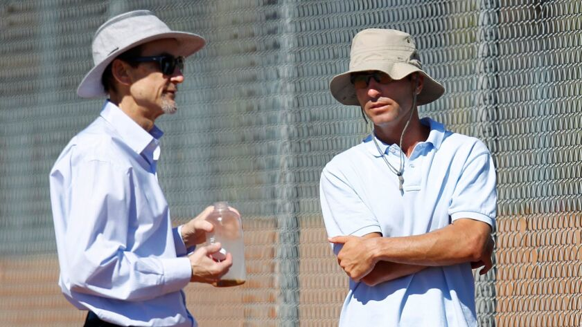 Padres General Partner Peter Seidler, left, and general manager A.J. Preller talk during a spring training practice in 2015.